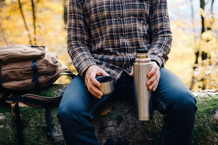 Unrecognizable young man resting in forest and holding cup and flask.