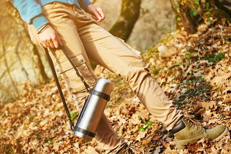 Female hiker holding flask outdoors in autumn forest, view of legs. Hiking and leisure theme