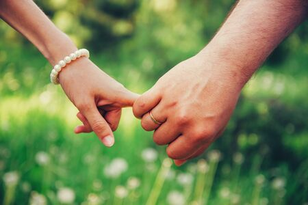 Young loving couple holding hands each other in summer park, view of hands