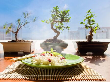 Rice with red asian berries goji. On background of bonsai