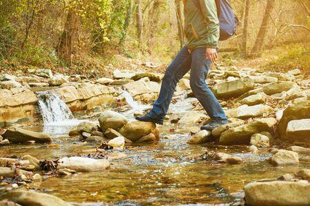 Wanderer mit Rucksack, der einen Fluss auf Steinen im Herbstwald überquert, Blick auf die Beine. Thema Wandern und Freizeit. Bild mit Sonnenlichteffekt
