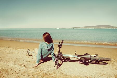 Young woman sitting near a bicycle on beach in summer