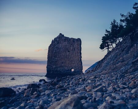 Rock Sail on pebble coast of Black sea in evening at sunset, Gelendzhik town, Russia