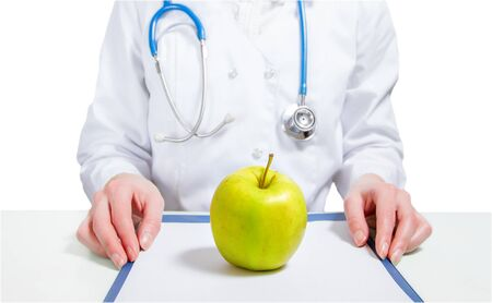 Apple on list, on the background of a woman doctor