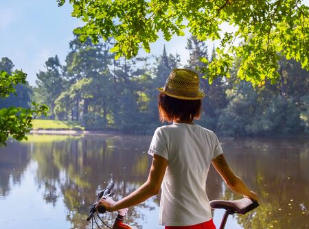 Young woman against river and nature background with bike