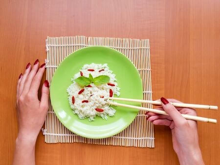 Woman is eating rice with berries, holding chopsticks. top view Imagens