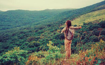 自由幸せな旅行者の女性は、腕を上げて立って、美しい自然を楽しんでいます。