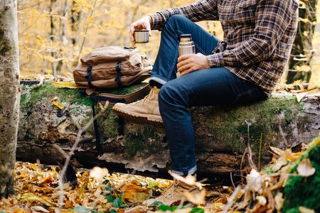 Unrecognizable young man resting with cup of tea in autumn forest. Banco de Imagens