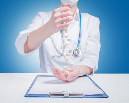 Pills fall from the hands of a doctor
