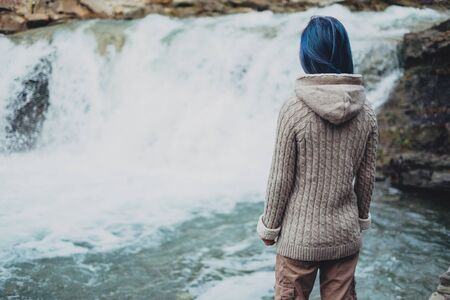 Traveler young woman with blue hair looking at beautiful waterfall, rear view Banco de Imagens - 128568219