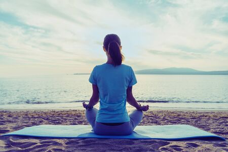 Giovane donna che medita in posa di loto sulla spiaggia vicino al mare in estate al mattino, vista posteriore Archivio Fotografico