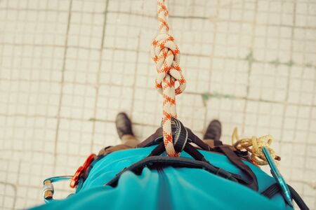 Climber man standing in harness with rope and knot Eight. Point of view shot. Top view