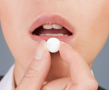Round white pill is on the lower lip, close-up
