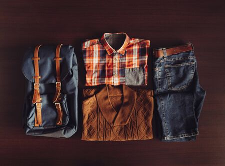 Set of male clothing and backpack in hipster style on wooden background, top view Stock Photo