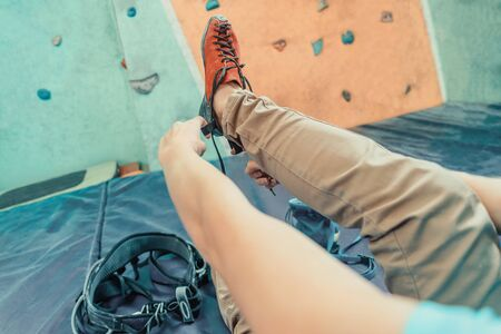 Young woman putting on climbing shoes and preparing to climb in gym, point of view shot 版權商用圖片