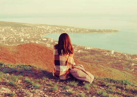 Young woman wrapped in plaid sitting on peak of mountain and enjoying view of sea.