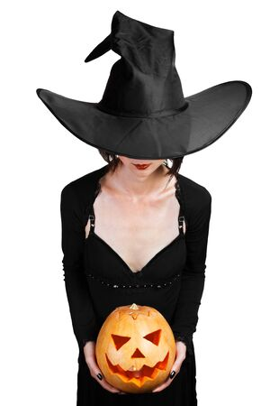 Halloween beautiful witch holding carved pumpkin on a white background