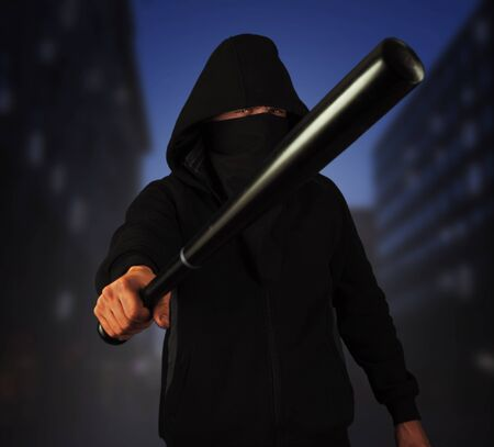 Dangerous man in the mask with baseball bat ready for fight in the night city Imagens