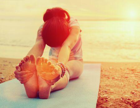 Giovane donna che fa esercizio di yoga sulla spiaggia estiva al tramonto. Immagine con effetto luce solare Archivio Fotografico
