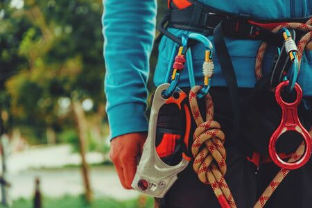 Rock climber wearing safety harness and climbing equipment outdoor, close-up image Imagens