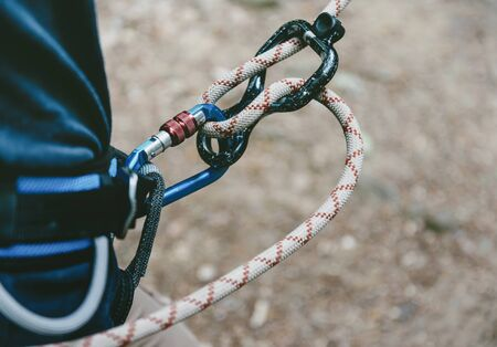 Female climber in harness with rope and figure eight. Imagens