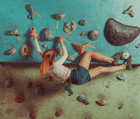 Little girl climbing on artificial boulders in gym
