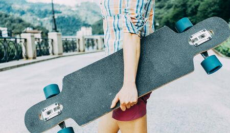 Unrecognizable teenager standing with longboard on street. Copy-space on surface of board.