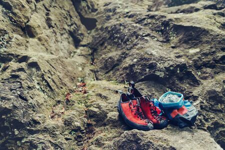 Climbing shoes and chalk bag with magnesium powder on stone rock outdoor