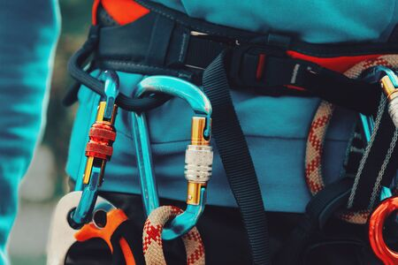 Close-up detail of rock climber wearing safety harness and climbing equipment outdoor