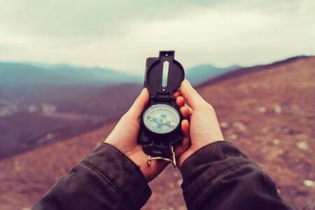 Kobieta turysta szuka kierunku z kompasem w górach. Strzał z punktu widzenia