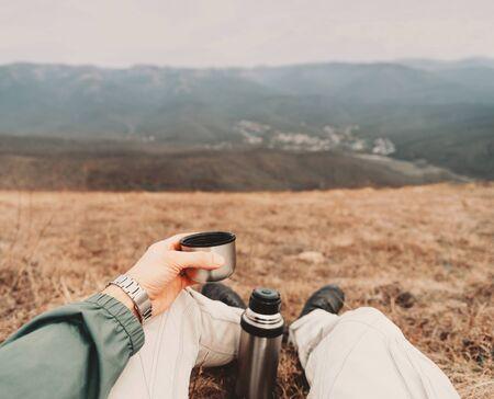 Uomo viaggiatore seduto con una tazza di tè e una boccetta in montagna. Scatto dal punto di vista