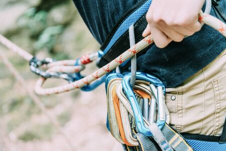 Sporty woman with climbing equipment belaying with rope and figure eight, close-up.