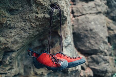 Red climbing shoes on stone rock otdoor