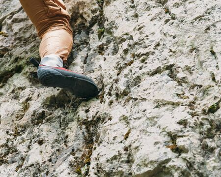 Woman climbing on rock. Close-up image of climber female foot on rock boulder outdoor