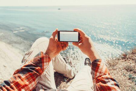 Hombre viajero tomando fotografías de mar con smartphone. Tiro del punto de vista