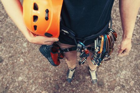 Woman with climbing equipment and helmet outdoor, top view. Face is not visible Imagens