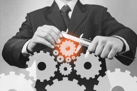 Unrecognizable businessman holds calipers with cogwheels, concept of business creation, monochrome image Banque d'images