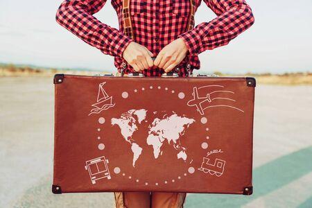 Reisende Frau, die mit einem Koffer steht. Weltkarte und Transportarten sind auf Koffer gemalt. Konzept der Reise