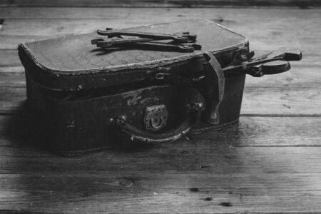 Working tools in vintage case on a wooden table. With film grain and low contrast effect. Black-white photo. Stockfoto