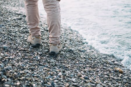 Unrecognizable woman walking on pebble coast near the sea, view of legs. Rear view
