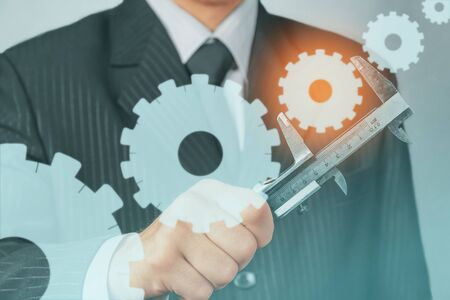 Unrecognizable businessman holds metal calipers with cogwheels, concept of business creation