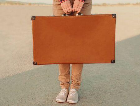 Viajero sosteniendo una maleta, vista de manos. Espacio para texto en maleta