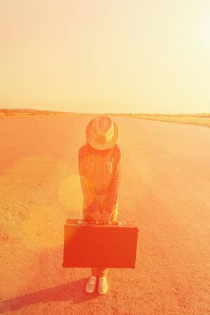 Traveler woman in hat stands on road with vintage suitcase, face is not visible. Space for text in the upper part of image. Image with sunlight effect