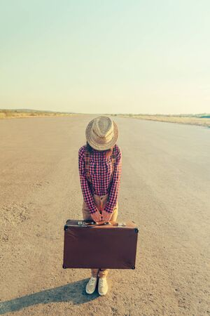 Traveler woman in hat stands on road with vintage suitcase, face is not visible. Space for text in the upper part of image Stock fotó