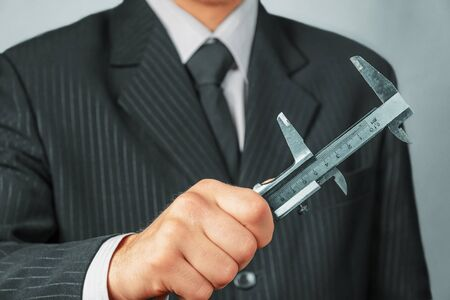 Unrecognizable businessman holds metal calipers, concept of business creation Stock Photo