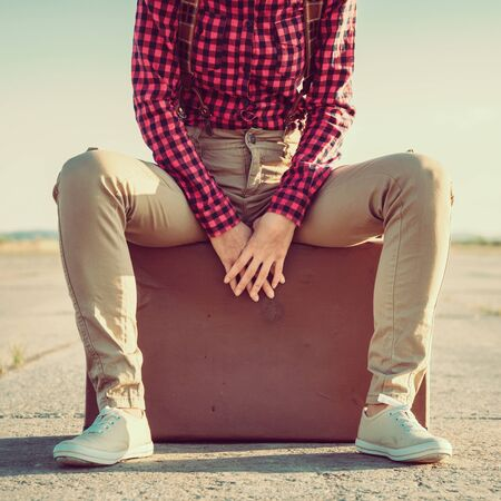 Unrecognizable woman sits on suitcase on road, space for text Banco de Imagens