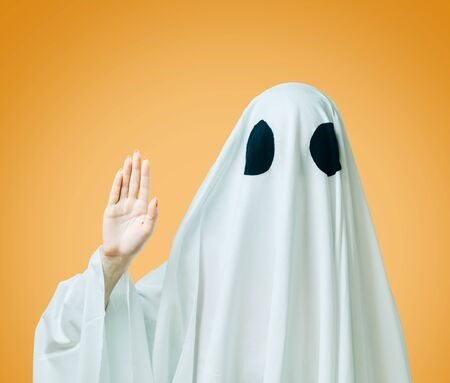Woman in a costume of white ghost wave his hand on yellow background.