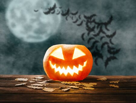 Spooky smiling glowing carved pumpkin in Halloween night on background of full moon and flock of bats.