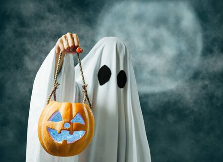 White ghost holding jack-o-lantern lighting pumpkin in Halloween full moon night. Stok Fotoğraf