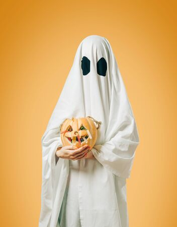 White ghost with Halloween trick-or-treat pumpkin basket on yellow background. Stok Fotoğraf